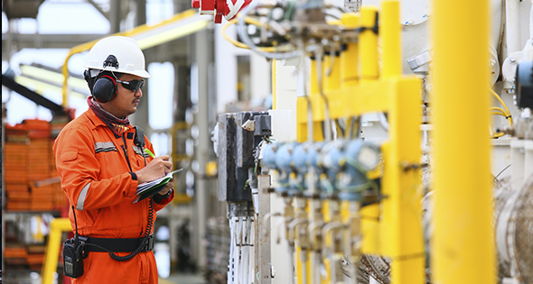 Homme en tenue de travail devant des canalisations de gaz (Istock)