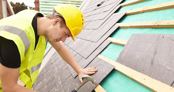 Couvreur en train de poser les dernières tuiles sur le toit d'une maison (Istock)