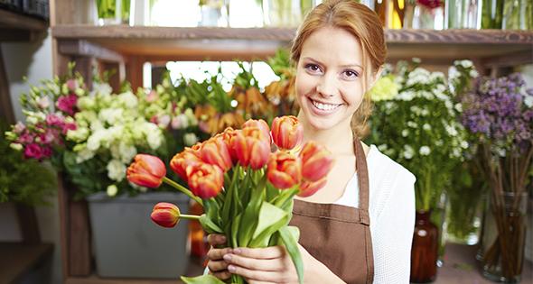 Fleuriste en train de proposer un bouquet de fleurs (Istock)