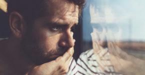 Homme triste regarde à travers la fenêtre