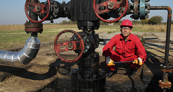 Technicien devant une canalisation de puits de pétrole (Istock)