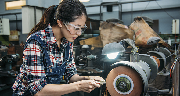Femme en train de polir une pièce mécanique (Istock)