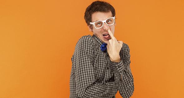 Homme qui louche avec un doigt dans le nez (Istock)