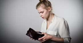 Femme inquiète fouillant son porte-feuille