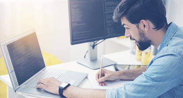 Jeune homme en train de travailler devant ses ordinateurs (Istock)