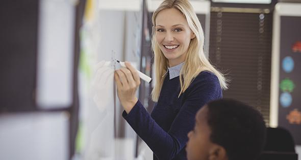 Professeur donnant un cours à un enfant sur un tableau (Istcok)